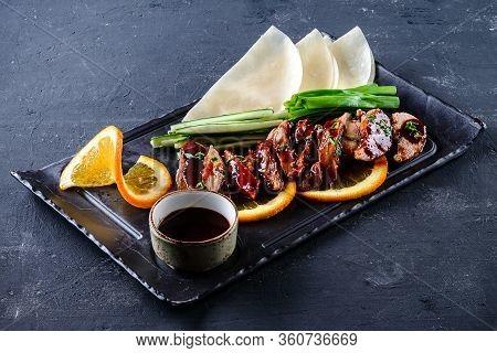 Peking Duck Set Served With Fresh Cucumber, Onion, Hoysin Sauce, Pancakes On Cutting Board On Dark B