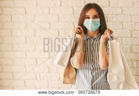 Happy Girl Shopper In Protective Face Mask With Paper Bags In Hands. Young Woman In Medical Face Mas