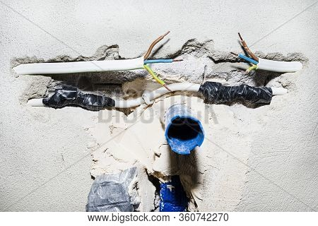 Cut Single-phase Cable In The Wall Of The House. Phase, Neutral And Ground Wire Visible.