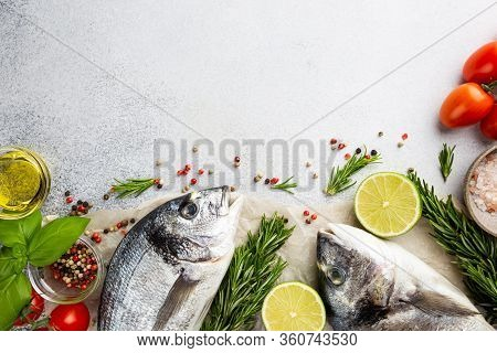 Fresh Ready To Cook Raw Bream Fish Dorado With Ingredients And Seasonings Like Rosemary, Salt, Peppe