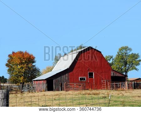 Arkansas Farm Site Has A Red Tin Covered Barn.  Tin Roof And No Loft Door.  Sky Is Blue.