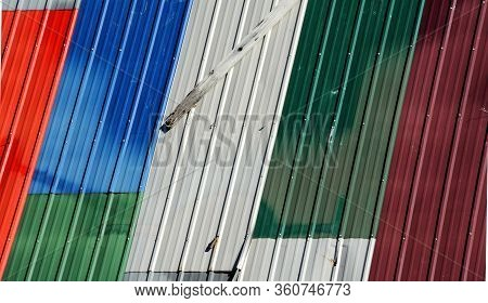 Shed Has A Conglomeration Of Different Colored Left Over Tin Roofing.  A Board Has Fallen Loose From