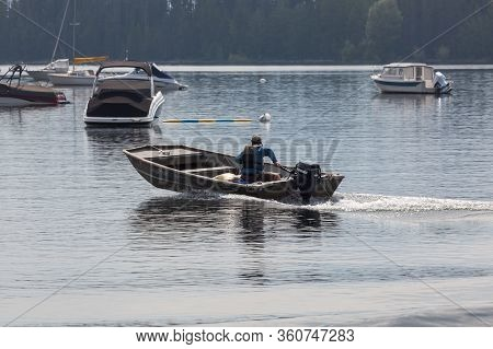 Grand Teton National Park, Wyoming / Usa - July 17, 2014:  A Man In A Small Boat Leaving Colter Bay