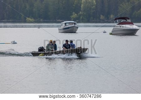 Grand Teton National Park, Wyoming / Usa - July 17, 2014:  Four Men In A Small Boat Coming Into Colt