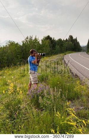 Grand Teton National Park, Wyoming / Usa - July 17, 2014: A Young Man With A Camera Taking Pictures
