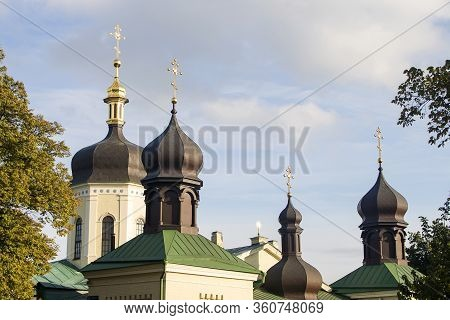 The Roof Of A Multi-domed Orthodox Church With Green Roofs And Black Domes Crowned With Gilded Cross