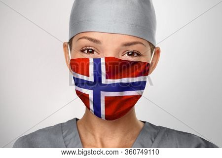 Norway COVID-19 doctor woman wearing PPE protective face mask with Norwegian flag for coronavirus prevention. Asian nurse happy. Health care worker helping.