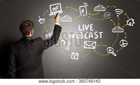 businessman drawing social media icons with LIVE WEBCAST inscription, new media concept