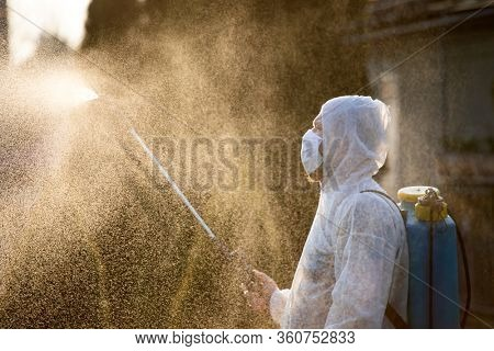 Man in protective equipment decontaminating and spraying on a public place as a prevention against Coronavirus disease 2019, COVID-19. Coronavirus pandemic.