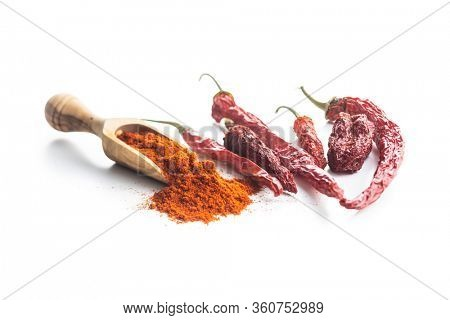 Dried red chili peppers and chili powder in wooden scoop isolated on white background.
