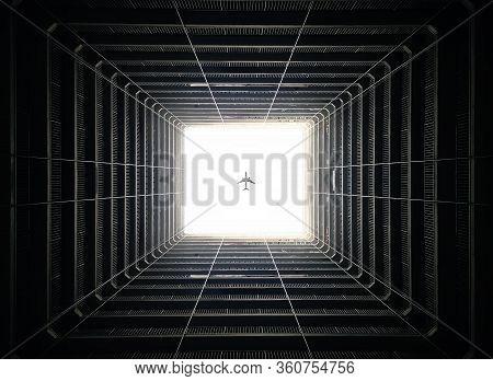 Passenger Plane Fly Overhead Through Dark Building Atrium Within Dark Shadows, Hong Kong
