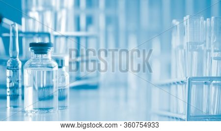 Serum Liquid Bottle On Table With Test Tube, Laboratory Research And Development Concept. Scientist