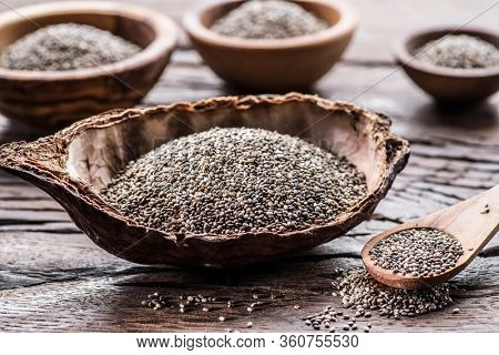 Chia seeds in different dishes on old wooden table.