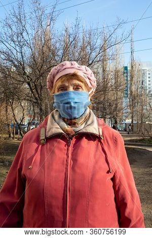 Portrait Of An Elderly Woman Wearing A Homemade Fabric Mask During A Covid-19 Outbreak. Safety In Pu