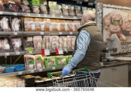A Bald Adult Man In A Medical Mask Chooses Chilled Meat Products In A Supermarket. Healthy Eating Ba