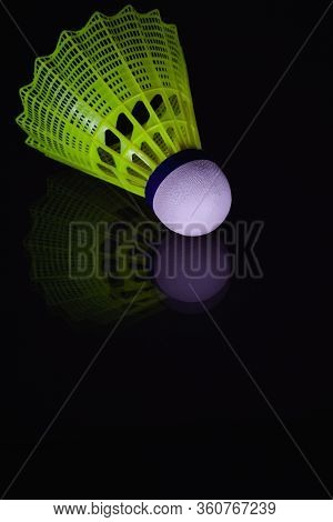 The Yellow Shuttlecock On The Black Background. Badminton Shuttlecock In Black Background With Refle