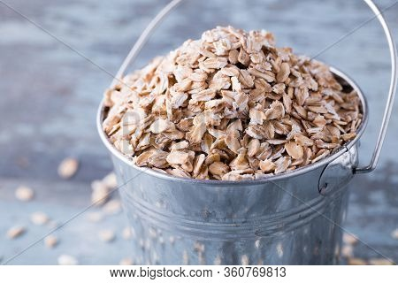Raw Oat Flakes In A Bucket On Wooden Background