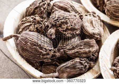Whole Black Cardamom In A Bowl On Wooden Background