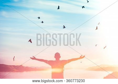 Happy Backpack Man Raise Hand Up And Birds Flying On Sunset Sky At River Background. Travel Adventur
