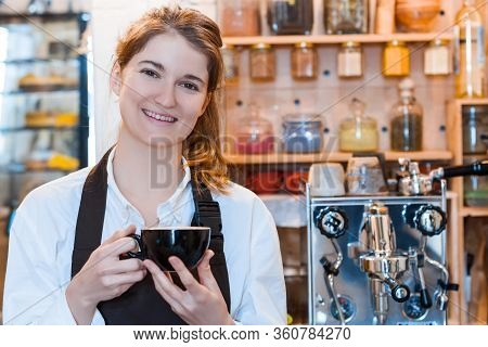 Young Woman Barista In Brown Apron Is Drinking Coffee On Workplace. Girl Is Waiting For Client In Ca