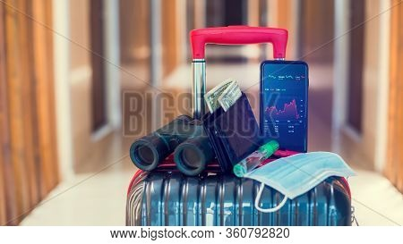 Red Graph On Smartphone With Medicine Mask, Wallet, Dollar Bill, Binoculars And Travel Equipment On
