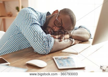 Taking A Break. Tired Afro American Man In Glasses Sleeping At His Working Place At Home. Afro Ameri