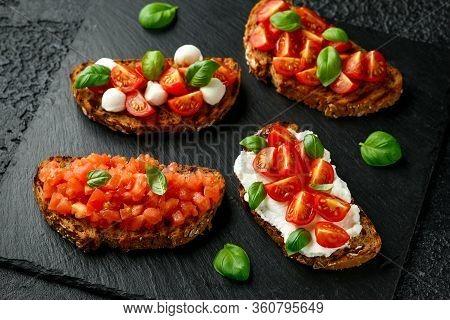 Bruschetta With Ricotta, Mozzarella Cheese, Basil, Cherry And Sliced Tomato On Rustic Stone Board