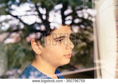 Kid Looking Out The Window At The Street Waiting For The End Of The Confinement Due To The Pandemic