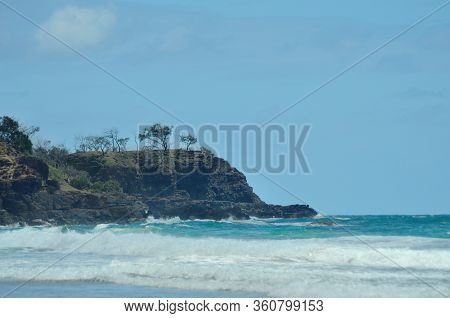 Waves Are Breaking Near A Rocky Headland, Which Is Covered With Trees. The Sky Is Blue With Faint Cl