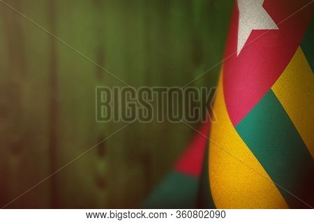 Togo Hanging Flag For Honour Of Veterans Day Or Memorial Day On Green Blurred Natural Wood Wall Back