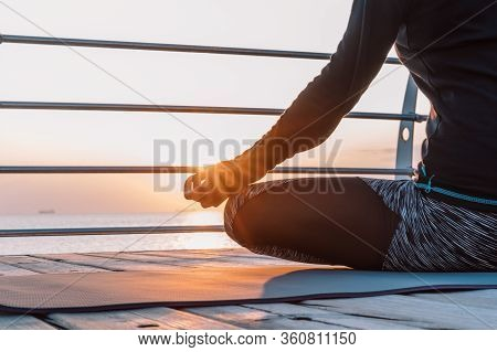 Concentrated Girl In Black Practicing In Yoga Meditation On Wooden Seafront. Woman In Lotus Pose. St