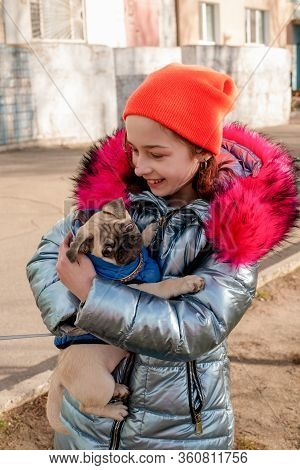 Cute Girl Relaxing With Her Pug Dog. A Girl Is Playing With A Pug Dog. Pet Love. Girl In Winter Clot