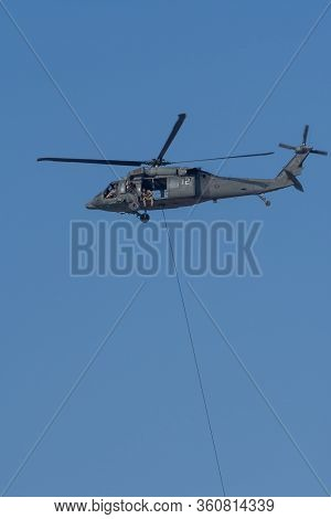 Military Team In Conflict Resucing People By Helicopter. Dropping A Rope Attached To Chopper In The