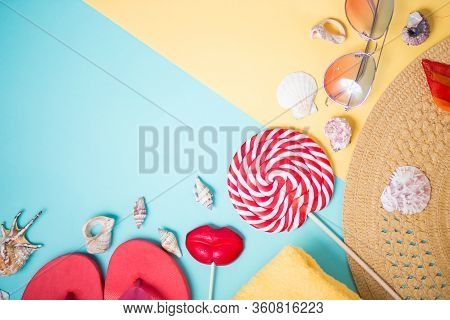 Beach Accessories On Mint Yellow Background With Copy Space. Top View Of Beige Straw Sun Hat, Towel,