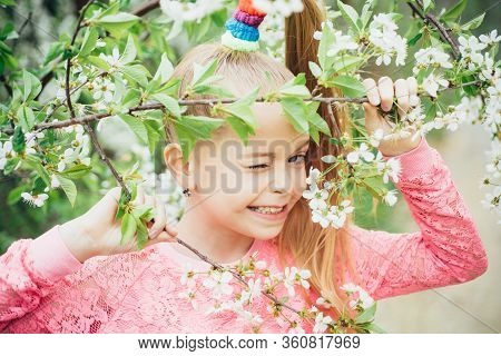 Portrait Of Funny Teenager Girl Winking At Camera Surrounded By Blooming Cherry Branches In Garden.