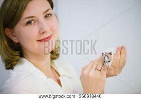 Girl Holds White Furry Little Mouse On White Background. Cute Young Mice In Hands Of Vet. Small Whit