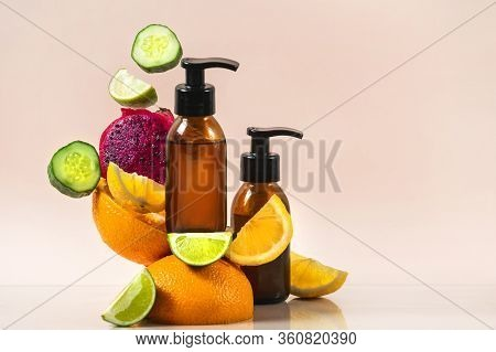 Bodycare Concept. Two Glass Bottle With Fresh Organic Cosmetics Near Levitate Citrus Fruit And Vitam