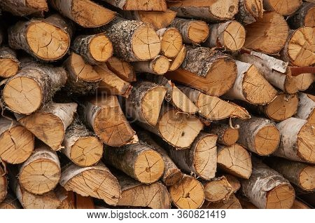 Firewood Harvested For The Winter Is Neatly Stacked In A Woodpile. Firewood For A Country House.