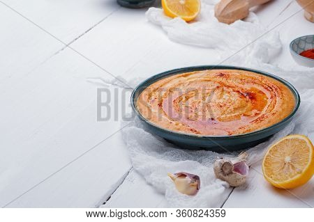 Hummus With Paprika In A Blue Plate On A White Wooden Background. Traditional Middle Eastern Hummus.