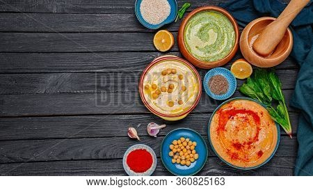 Colorful Hummus Bowls, Healthy Vegan Dips On A Black Wooden Background. Hummus With Spinach, Paprika