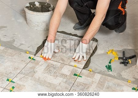 A Worker Is Installing Ceramic Tiles On The Floor.