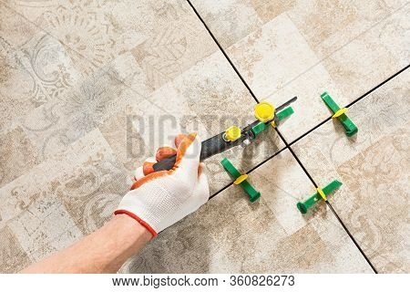 A Worker Is Leveling The Ceramic Tile With Wedges And Clips.