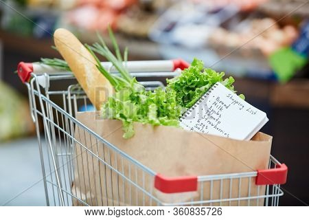 Background Image Of Shopping Cart With Fresh Groceries, Focus On Shopping List In Paper Bag, Copy Sp