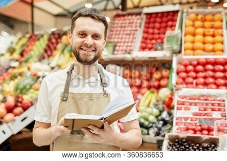 Waist Up Portrait Of Bearded Man Wearing Apron And Smiling At Camera While Standing By Fruit And Veg