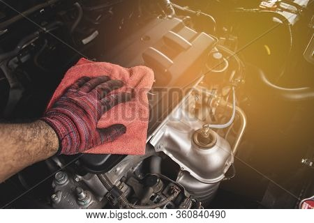 Hand Is Cleaning Engine Cover With A Using Red Microfiber Cloth,automotive Maintenance Concept.