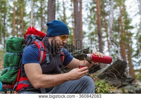 A Male Tourist Pours Tea From A Thermos During A Halt In The Forest. Active Lifestyle And Health Con