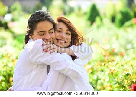 Girl Friends Hugging Outdoors. Women Are Hugging On The Green Field. Embrace Concept. Smile And Enjo