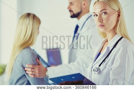 Handsome male doctor consulting a couple about infertility in his medical office