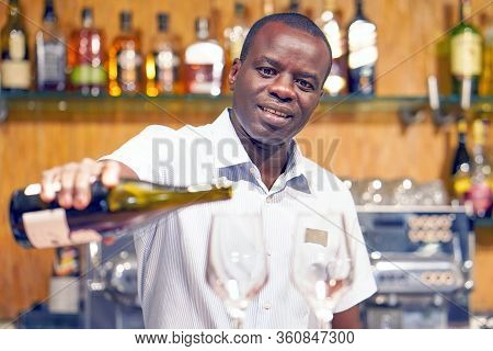 Elderly African Bartender Man Standing, Pours Red Wine Into A Glass From A Bottle. Shelves With Bott