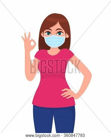 Happy Young Girl Wearing Medical Face Mask And Showing Okay Sign With Hand Fingers. Trendy Woman Cov